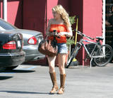 Hillary Duff shows legs in denim shorts, orange top and boots in Toluca Lake in Los Angeles